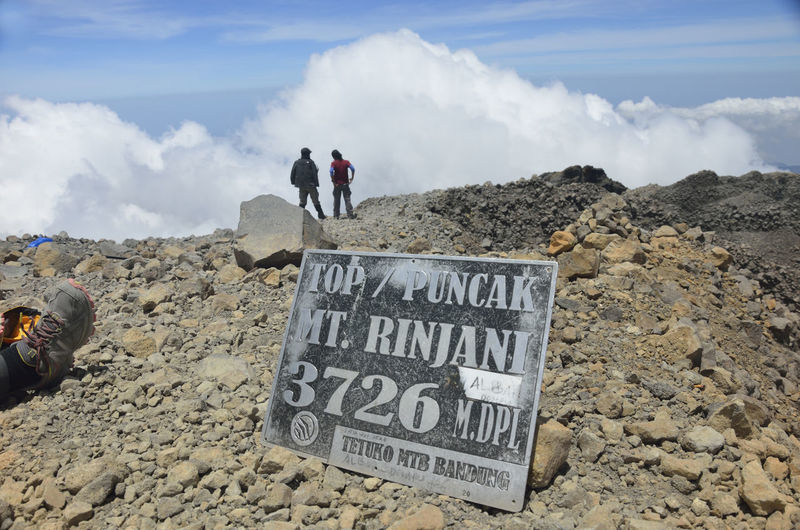 Information sign on mountain peak by hikers against sky