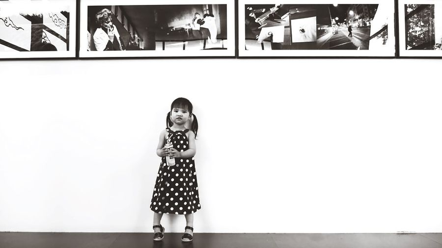 Portrait of girl standing against wall at home