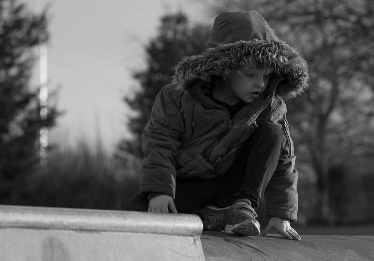 Full length of boy in warm clothing kneeling on footpath against trees