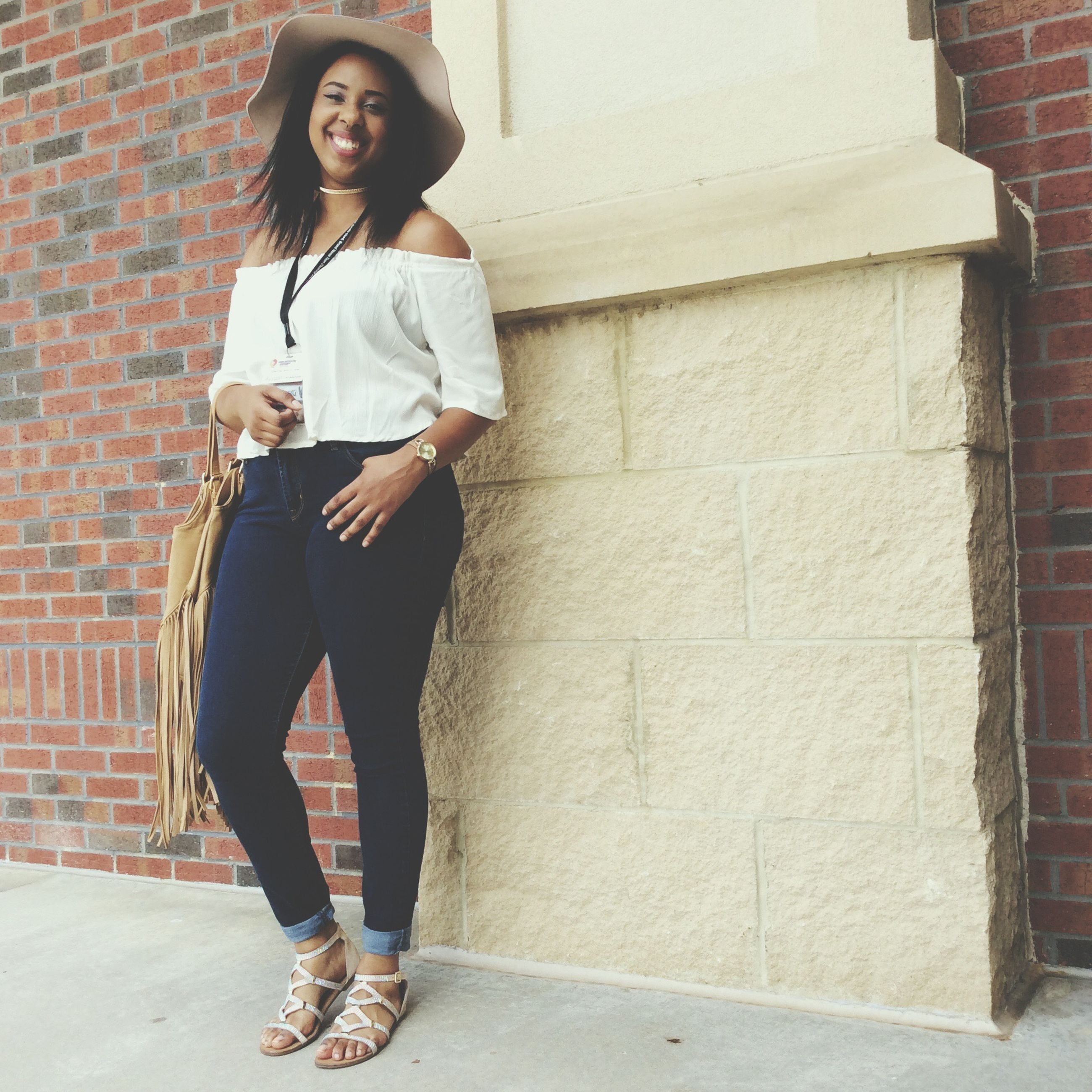 full length, standing, casual clothing, architecture, built structure, young adult, young women, brick wall, wall - building feature, person, leisure activity, lifestyles, portrait, building exterior, front view, looking at camera, t-shirt, long hair, day, confidence, outdoors