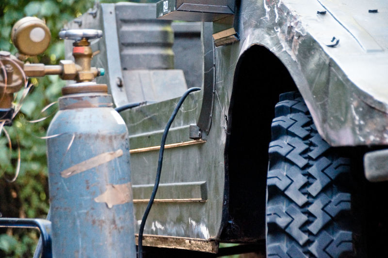 Close-up of gas cylinder by vehicle