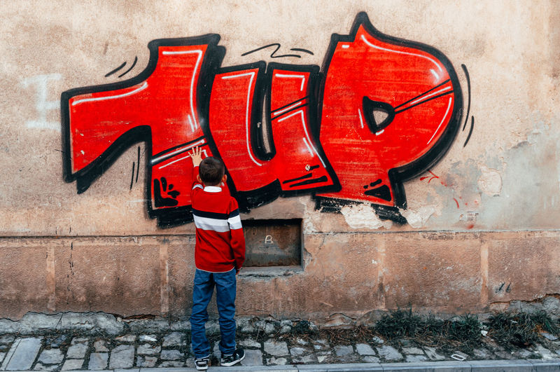 Full length of man standing on red wall