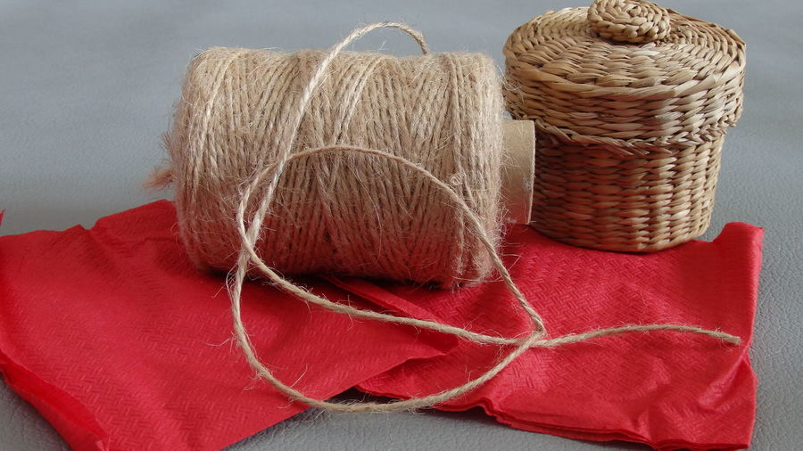 Close-up of spool by wicker basket on table