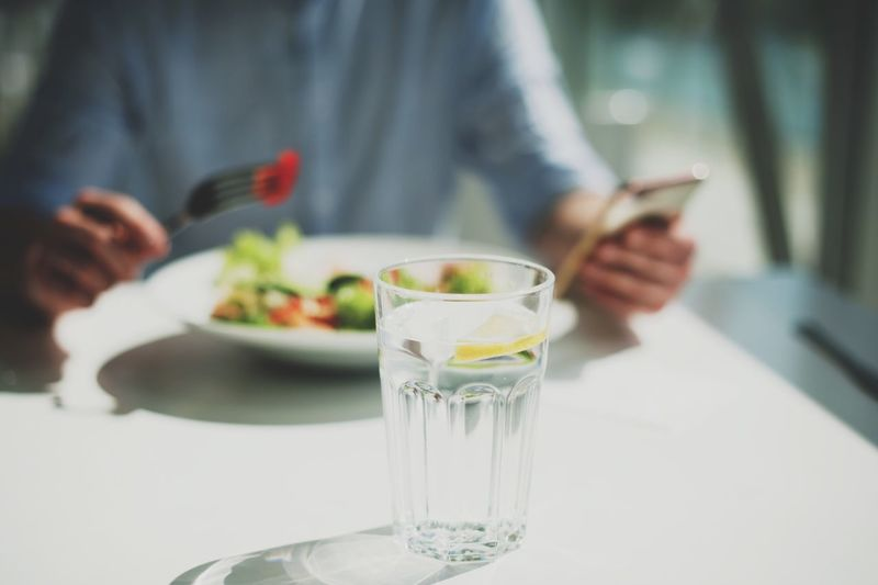 a young man eats a salad in a light restaurant Glass Midsection Focus On Foreground Holding Table Food And Drink One Person Drinking Glass Women Freshness Hand Indoors  Drink Human Hand Real People Lifestyles Adult Household Equipment Refreshment