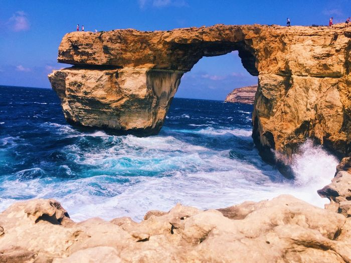 Scenic view of natural arch against blue sky