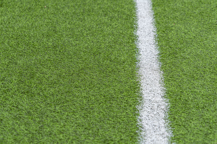 Green artificial grass soccer sports field with white stripe line.