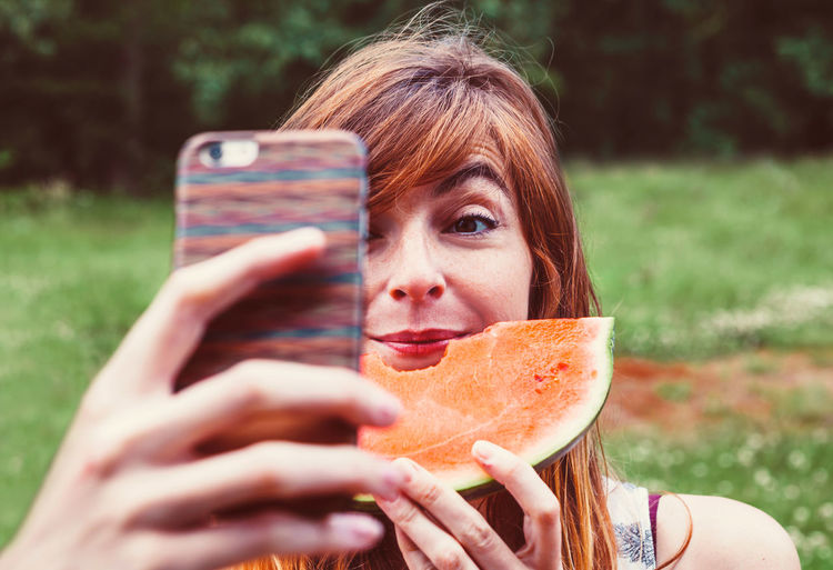 Woman photographing while eating watermelon