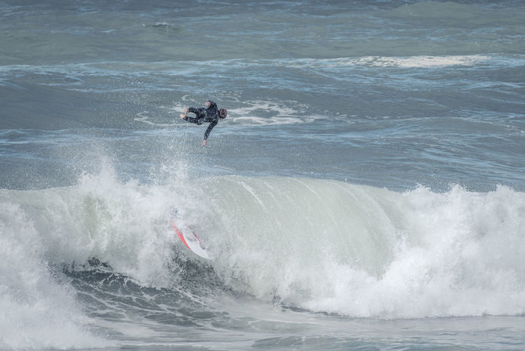 Surfer In Mid-Air Over Sea Waves