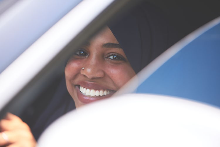 Close-up portrait of smiling young woman in car