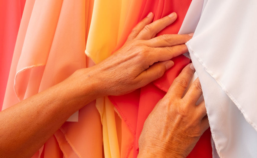 Cropped hand of man choosing textile in store