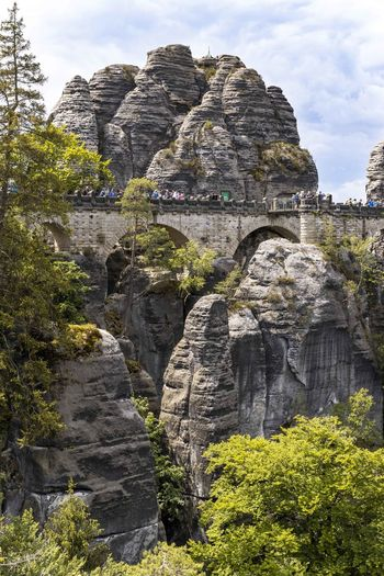 Low angle view of rock formations with a bridge on mountains