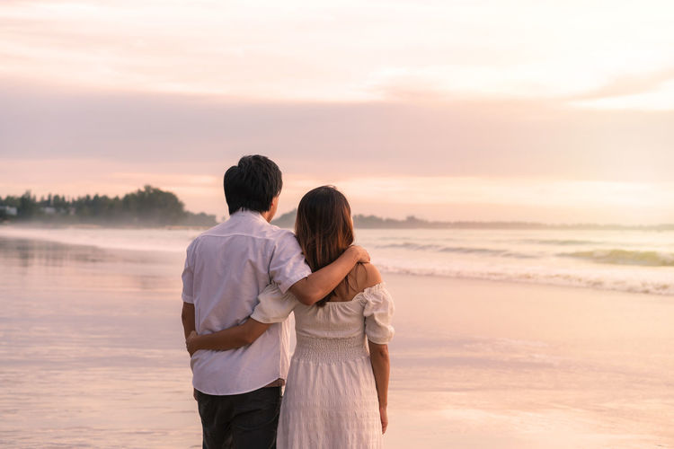 Couple standing on shore against sky during sunset
