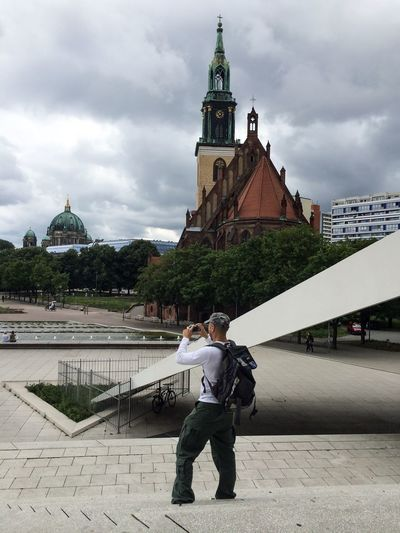 Rear View Of Man Photographing St Mary Church And Berlin Cathedral Against Cloudy Sky
