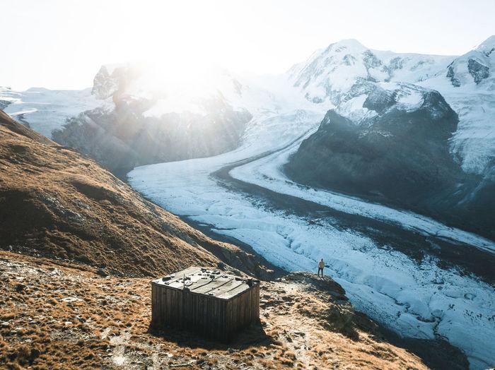 A hiker watching the sun come up over the gorner glacier near zermatt, switzerland.