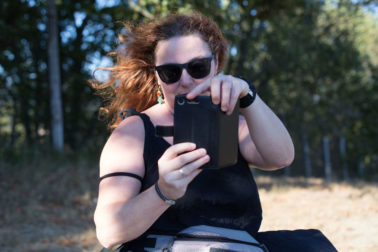 Midsection of woman holding sunglasses on land