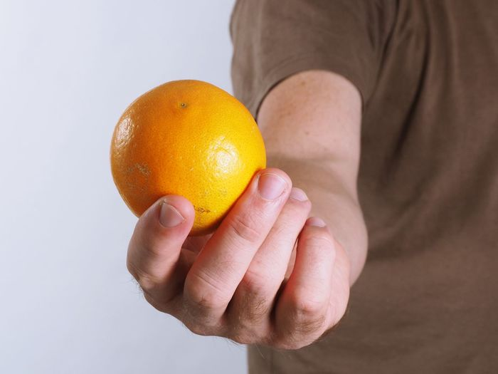 Close-up of hand holding fruit against white background