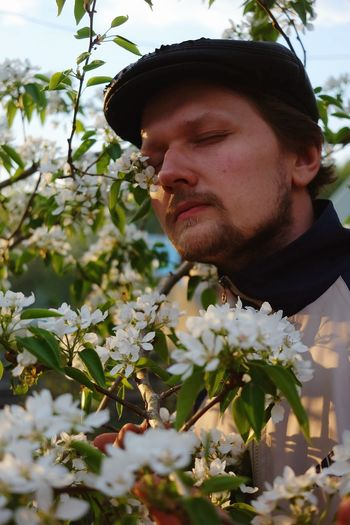 Portrait of young man looking at flowering plant