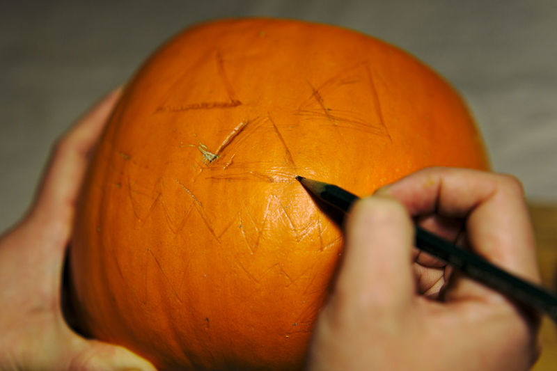 Cropped hands marking on pumpkin during halloween
