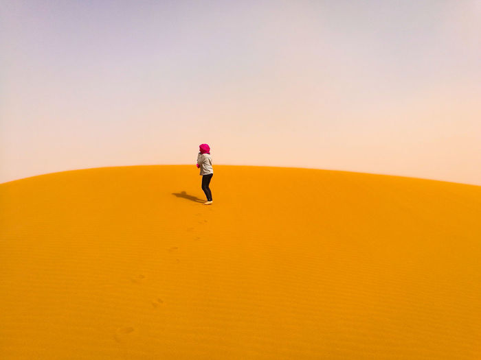 Woman Standing On Sand Dune Against Sky At Desert