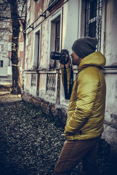 Adult Architecture Building Exterior Camera - Photographic Equipment Cap Day Holding Lifestyles Men One Person Outdoors People Photographer Photographing Photography Themes Real People Technology Women