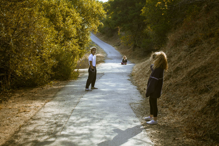 Casual Path Casual Clothing Day Full Length Leisure Activity Lifestyles Nature Nature Walk Outdoors Real People Staggered Sunlight And Shadow Three People Togetherness Tree Walking Walkway Women Young Adult Young Women