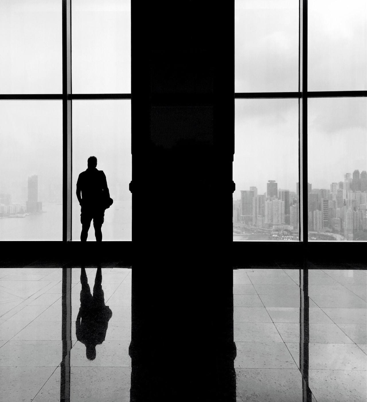 Silhouette man looking through window in building
