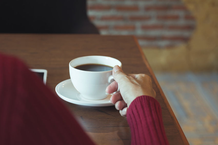Female's hand holding a coffee cup on wooden table. Human Hand Drink Cup Hand Mug Coffee Coffee Cup Food And Drink Coffee - Drink Refreshment One Person Holding Human Body Part Table Real People Lifestyles Leisure Activity Adult Saucer Crockery Hot Drink Tea Cup Non-alcoholic Beverage Finger
