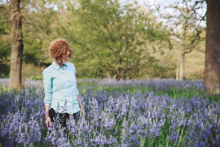 Woman standing amidst purple flowering plants at forest