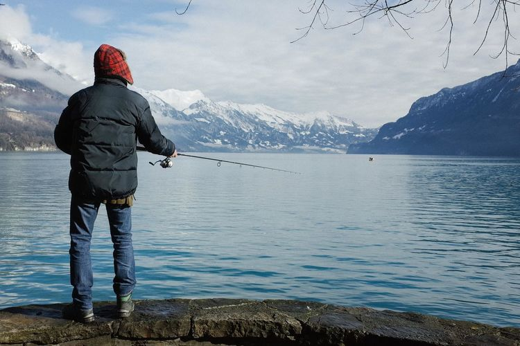 Rear view of person fishing at sea shore against snowcapped mountains