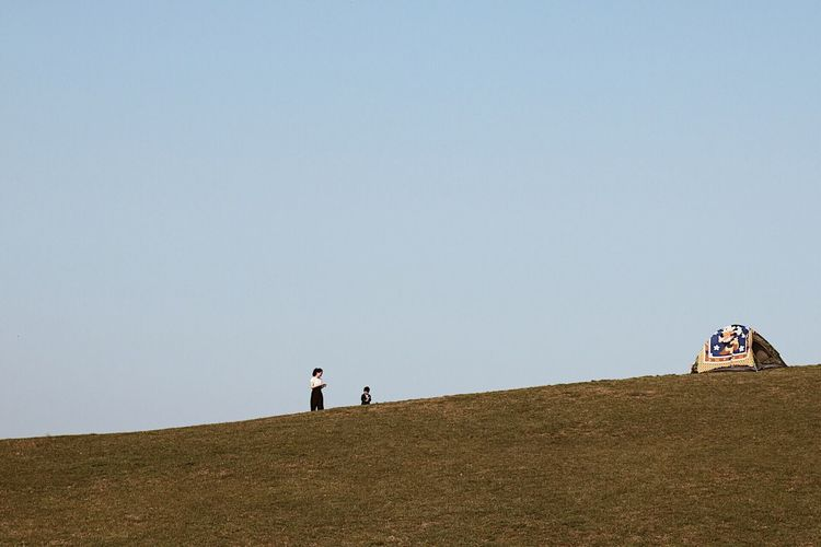 Men on landscape against clear sky