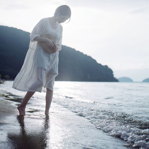 Water One Person Sea Real People Lifestyles Leisure Activity Sky Non-urban Scene Beauty In Nature Mountain Scenics - Nature Standing Nature Women Outdoors Full Length Day Beach Land