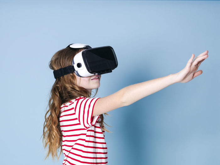 smiling positive girl wearing virtual reality glasses goggles headset, vr box. connection, modern, new generation, concept. girl trying to touch objects in virtual reality, studio shot on blue background Cyberspace Goggles Virtual Glasses Simulation Girl Entertainment Future Generation 360 3D Box Design Business Fun Joyful Gaming Game Electronic Futuristic Blue Copy Space Experience Young Human Woman Model Visual Viewer Video Film Look Observe Learn Pupil School Funny Technology Technical University  Visions Safety Glasses Glass Cool Female One Translated With Www.DeepL.com/Translator Childhood Virtual Reality Simulator Child Leisure Activity Women Striped One Person Standing Real People Waist Up Lifestyles Casual Clothing Offspring Females Girls 3-d Glasses Hairstyle Innocence