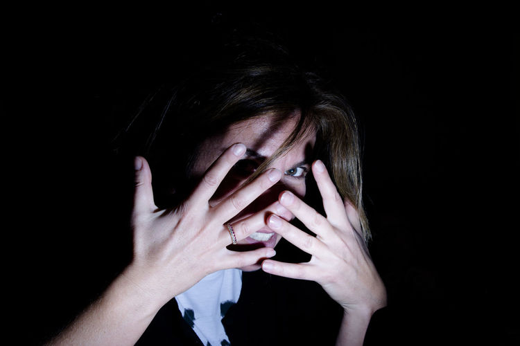 Portrait of woman covering her face with hands in darkroom