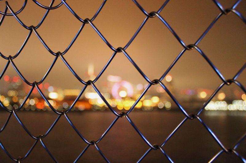Full frame shot of chainlink fence against sky during sunset