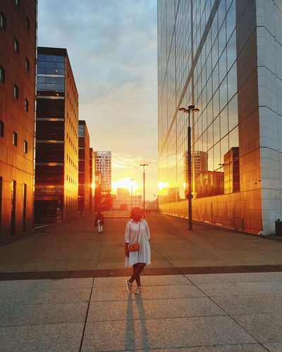 Woman standing on street amidst buildings in city during sunset