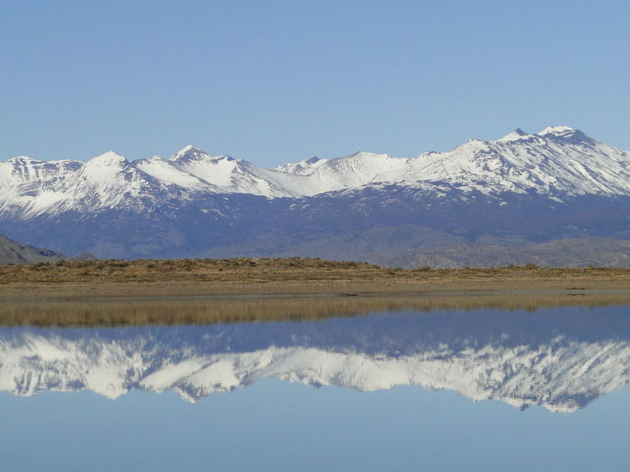 Scenic reflection of snowed mountains in calm lake
