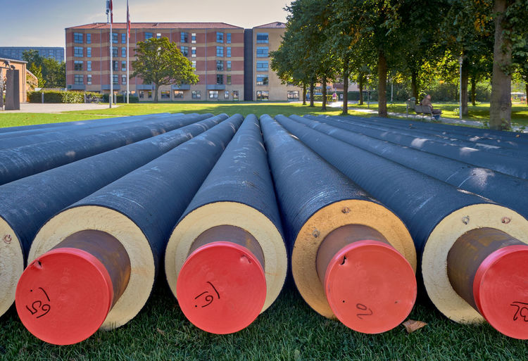 PIPING HOT: Copenhagen has lots of district heating. Rødovre, København, Denmark. Pipes Heating Receding Architecture Building Building Exterior Built Structure City Communication Day Field Fuel And Power Generation Grass In A Row Industry Multi Colored Nature No People Outdoors Plant Red Side By Side Tree
