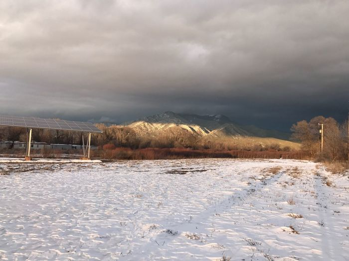 Scenic view of frozen lake against storm clouds
