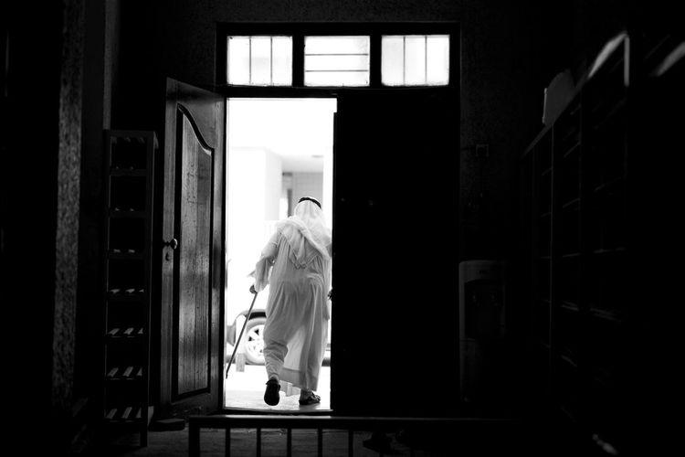 Rear view full length of senior man walking at mosque doorway