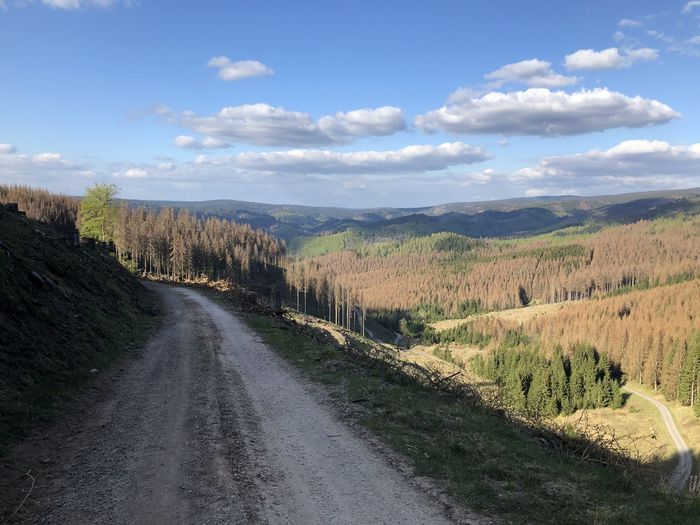 Dirt road along landscape and against sky