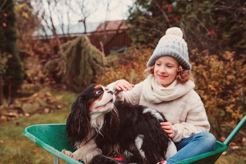 Girl Sitting With Dog In Wheelbarrow On Field