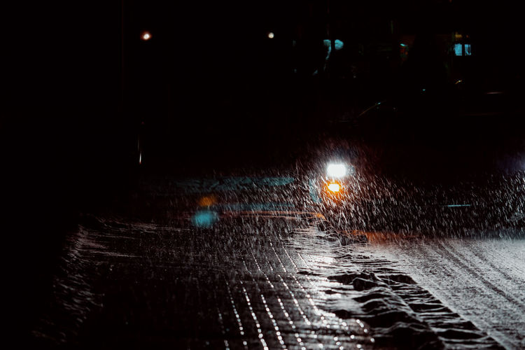 SMALL BLIZZARD Night Illuminated Street Transportation City Mode Of Transportation Road No People Land Vehicle Outdoors Light Winter Snow Traffic Wet Street Light Rain Motor Vehicle Architecture Car Direction Lighting Equipment Nature Dark Rainy Season Surface Level RainDrop