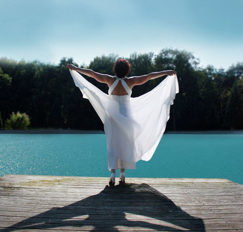 Arms Spread Bathing In The Sun Beauty In Nature Blue Lake Day Full Length Low Section Luxury Nature One Person Outdoors People Rear View Shadow Sky Summer Sunlight Tree Vacations Water White Color White Dress Young Adult Young Women
