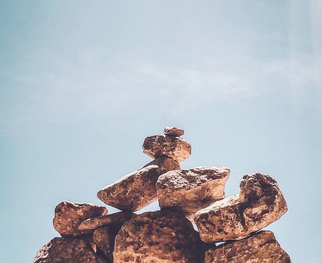 Low angle view of stack on rock against sky
