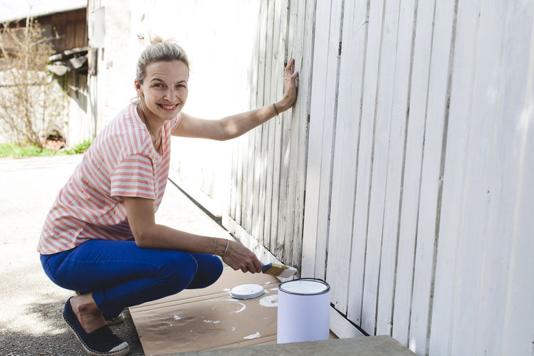 Portrait of smiling woman painting wooden wall