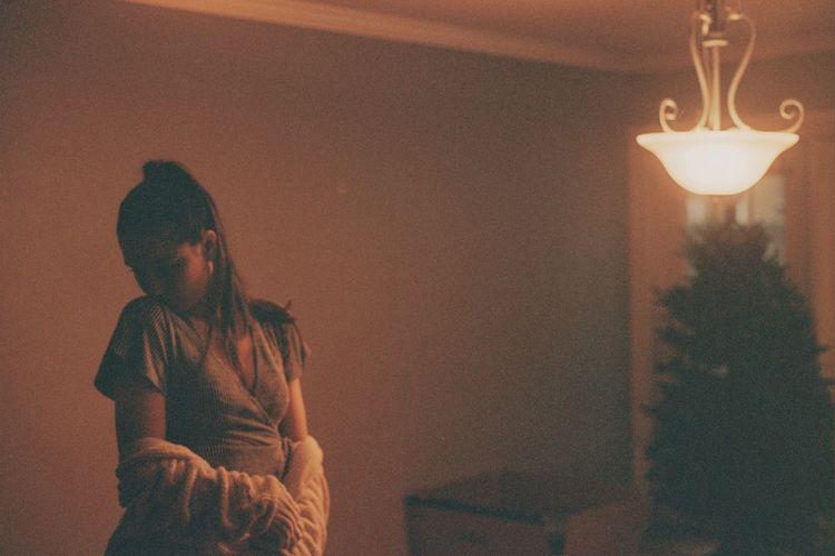 Woman looking at illuminated christmas tree at home