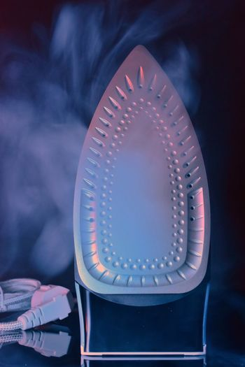 Close-up of steam iron against black background