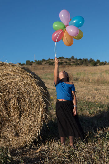 Rear view of man with balloons in field