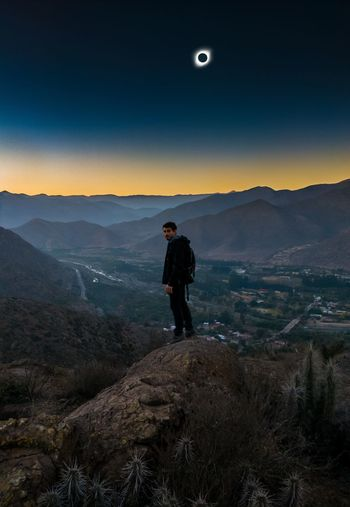 Man standing on mountain peak against eclipse