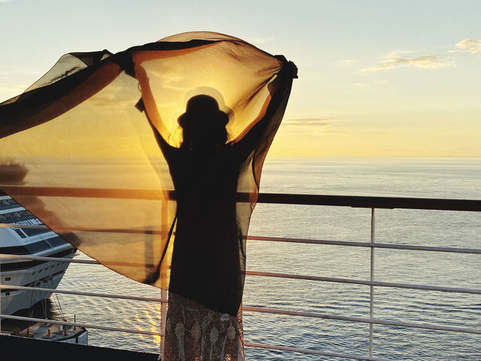 Rear view of woman holding fabric while standing by railing against sea and sky during sunset